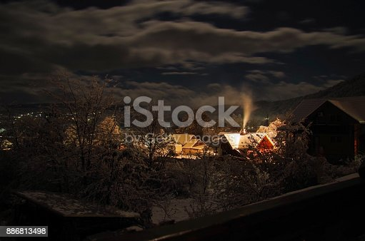 istock 4 Seasons. Christmas fairy tale. Winter night. Smoking chimney of house in mountain village. Nature and travel. Russia, Adygea, Caucasus Mountains 886813498