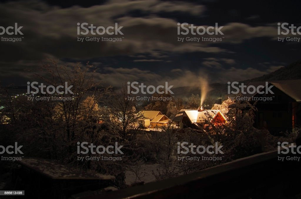 4 Seasons. Christmas fairy tale. Winter night. Smoking chimney of house in mountain village. Nature and travel. Russia, Adygea, Caucasus Mountains stock photo