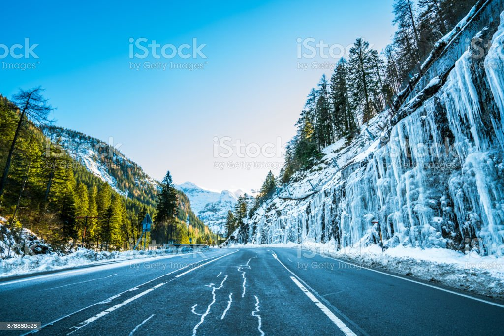 4 Seasons - early onset of winter, country road with icicles in mountains stock photo