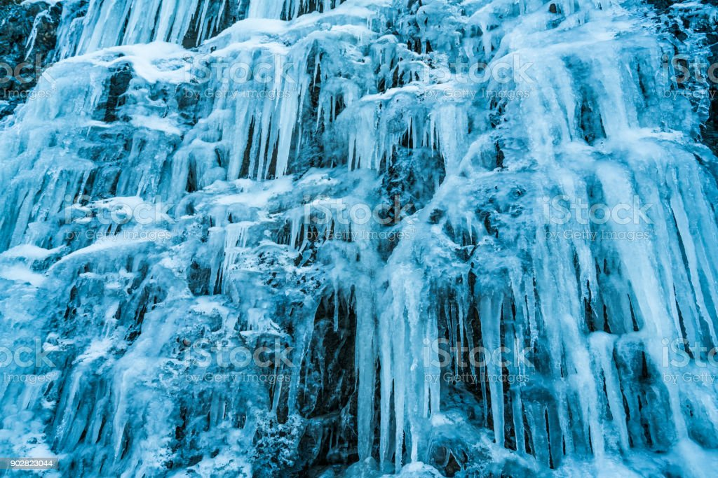 4 Seasons - many huge icicles over rock face on cold winter day stock photo