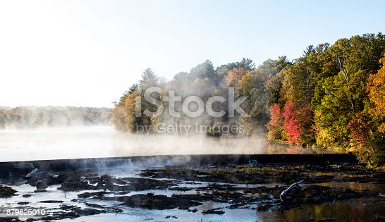 A steaming river in the early morning light with Autumn color along the bank on a cold morning on the Wallkill river in New York.