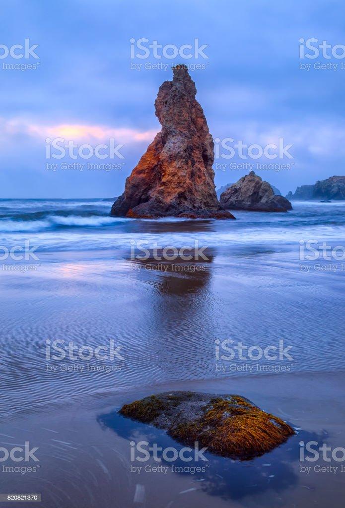 Seastack at Bandon Beach in Bandon, Oregon at sunset. stock photo