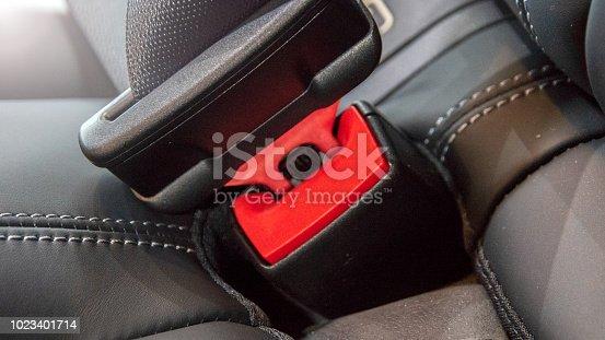 Seat belt on a black leather seat.