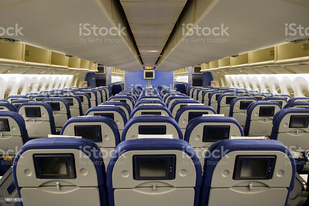 Seat rows with video screens inside an airplane stock photo