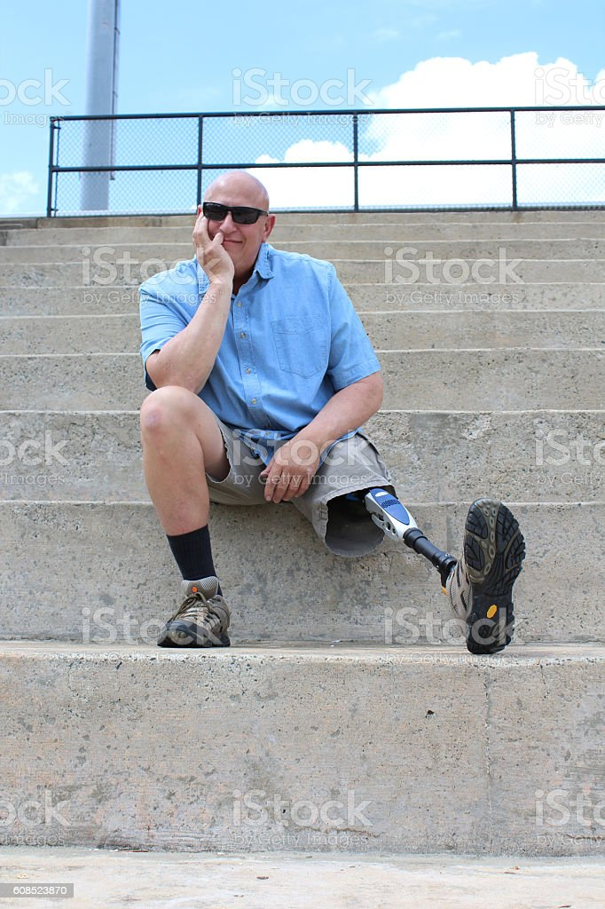 Seated amputee man with prosthetic leg outstretched stock photo