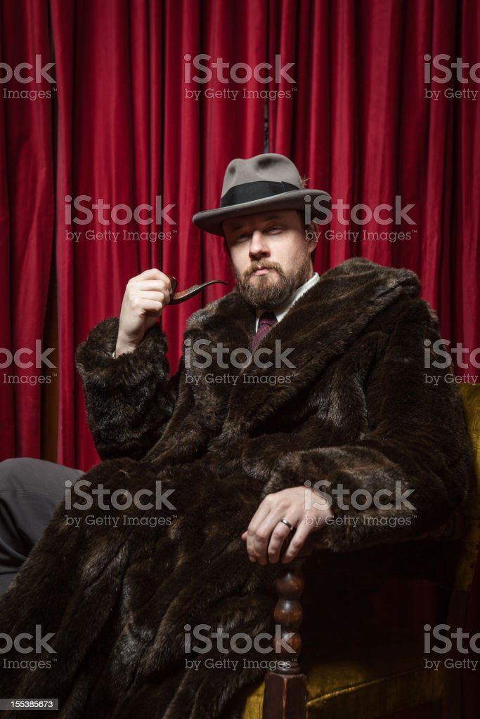 Seated Bearded Man Wearing Fedora, Fur Coat, Holding Pipe royalty-free stock photo