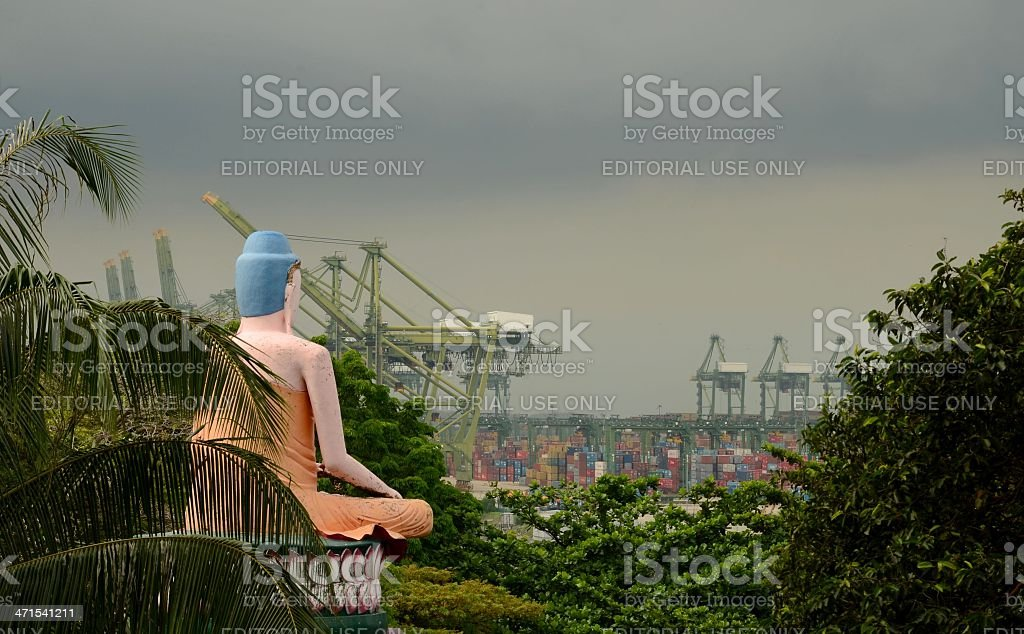 Seated meditating Buddha views busy container seaport stock photo
