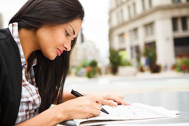 sitzende frau schaut durch arbeit oder real estate einträge - immobilienangebote stock-fotos und bilder