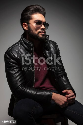 istock seated young man in leather jacket and sunglasses 469743723