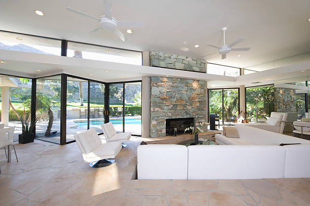 Seating Area And Stone Fireplace In Spacious Living Room Sunken seating area and exposed stone fireplace in spacious living room with view of swimming pool at home sunken stock pictures, royalty-free photos & images