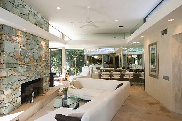 Seating Area And Stone Fireplace Sunken seating area and stone fireplace with dining area in background at home sunken stock pictures, royalty-free photos & images