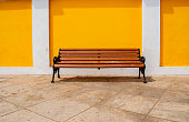 seats against yello wall in Pondicherry, India