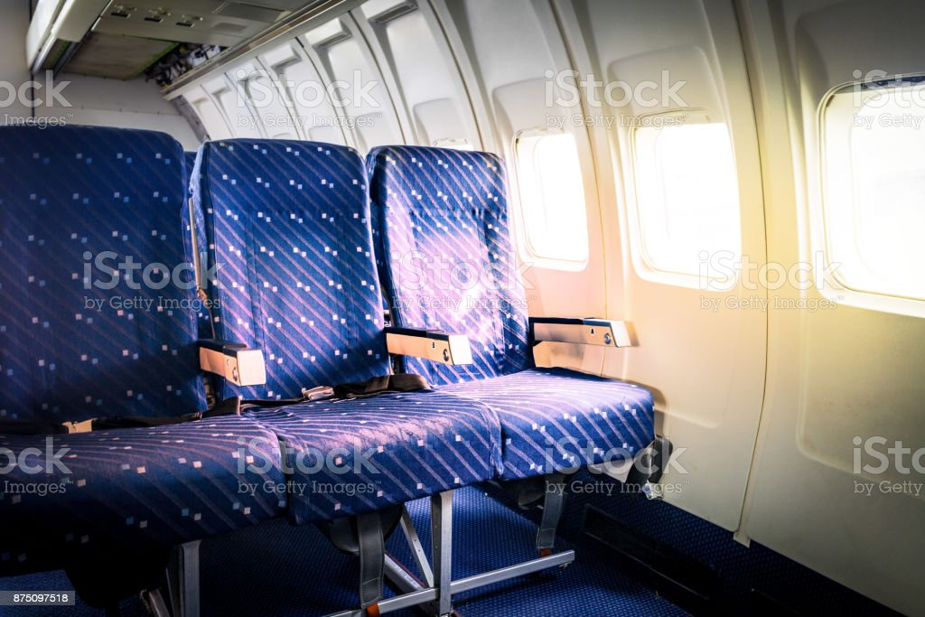 Seats in commercial aircraft cabin with sun light shining through the windows stock photo