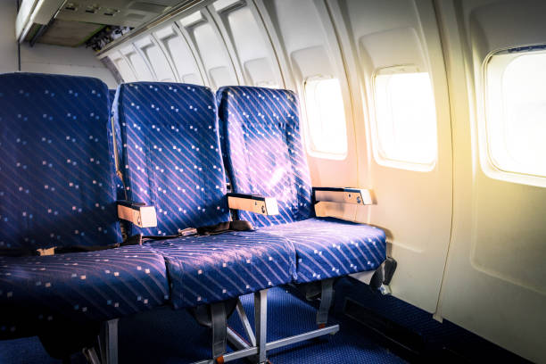 Seats in commercial aircraft cabin with sun light shining through the windows Seats in commercial aircraft cabin with sun light shining through the windows airplane seat stock pictures, royalty-free photos & images