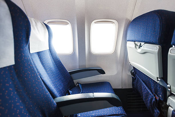seats in economy class section of airplane blue seats in economy class passenger section of airplane airplane seat stock pictures, royalty-free photos & images