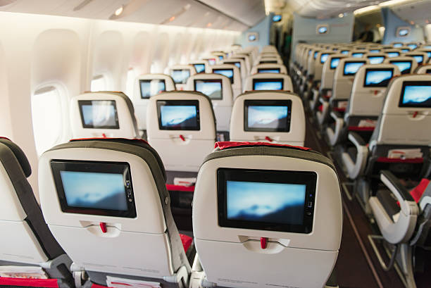 Seats on board of airplane. Economy class with screens - Photo