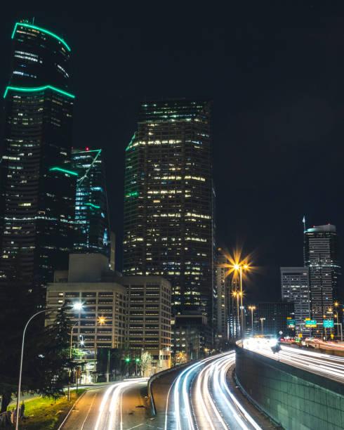 Seattle Cityscape Skyscraper Buildings Above Freeway Long Exposure Car Streaks at Night stock photo