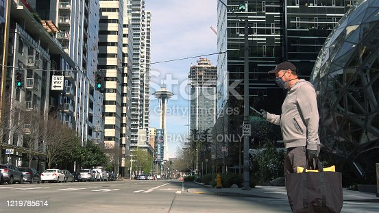 Seattle, WA - April 17th, 2020: A man wearing face mask is crossing a quiet downtown street during the Covid-19 stay-at-home emergency.