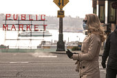 Seattle, USA – Feb 29, 2020: Late in the day a woman in downtown near the public market wearing a face mask protecting herself from the spreading Coronavirus that originated in Wuhan China.