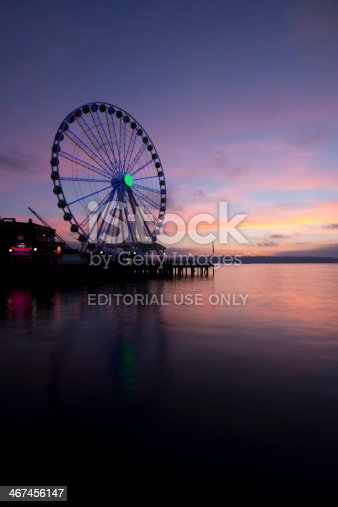 Seattle, USA - January 17, 2014: The Seattle Ferris Wheel illuminated on Elliott Bay in downtown Seattle at sunset with a vivid pink sky.