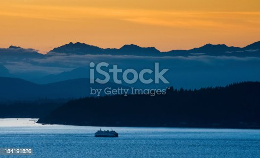 A Washington State Ferry sails past Bainbridge Island at sunset with the Olympic Mountains in the background.