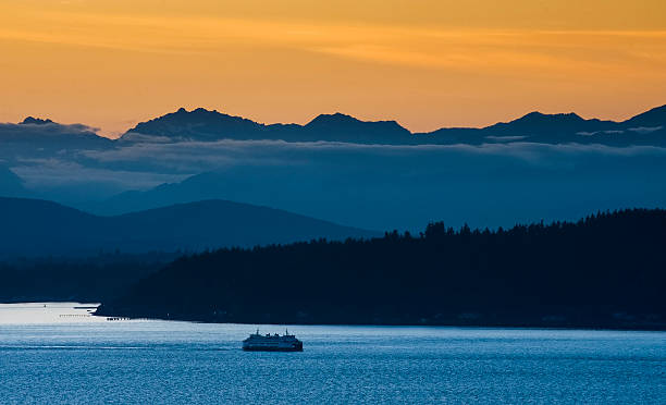 Seattle Ferry and the Olympic Mountains. A Washington State Ferry sails past Bainbridge Island at sunset with the Olympic Mountains in the background. washington state stock pictures, royalty-free photos & images