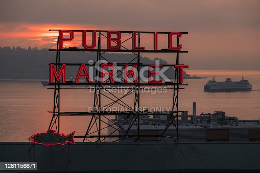 Seattle, USA - Nov  22, 2019: The famous neon public market sign at Pike Place Market with a Washington state ferry passing on Elliott bay at sunset.
