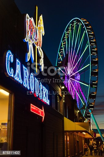 Seattle: Neon lights of Pier 57 as people visit the Ferris Wheel at twilight.