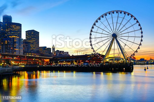 Seattle, Washington, USA - December 13, 2017: Seattle seaport sunrise with Pier 57 shops, Ferris wheel, and Seattle skyline on the background