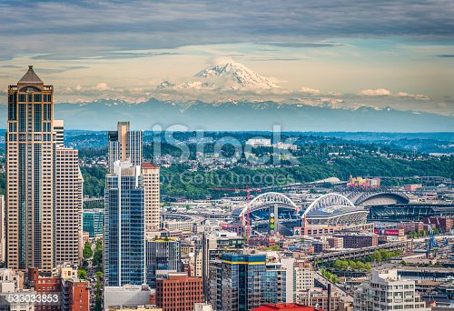 Aerial view over the skyscrapers and landmarks of downtown Seattle, overlooked by the iconic snow capped pyramid of Mt. Rainier (14,411ft). ProPhoto RGB profile for maximum color fidelity and gamut.