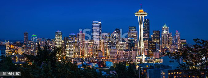 Panoramic view across skyline of Seattle, the iconic spire of the Space Needle and the crowded skyscrapers of downtown brightly illuminated against the blue dusk sky, Washington, USA. ProPhoto RGB profile for maximum color fidelity and gamut.