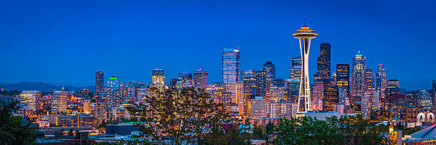 Seattle Space Needle downtown skyscrapers illuminated dusk panorama Washington USA Panoramic view across skyline of Seattle, the iconic spire of the Space Needle and the crowded skyscrapers of downtown brightly illuminated against the blue dusk sky, Washington, USA. ProPhoto RGB profile for maximum color fidelity and gamut. puget sound stock pictures, royalty-free photos & images