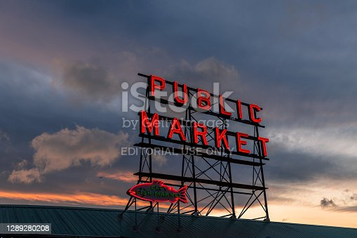 Seattle, USA - Jan 5, 2019: A vivid sunset with the landmark neon public market sign on Pine street at Pike Place Market at sunset.