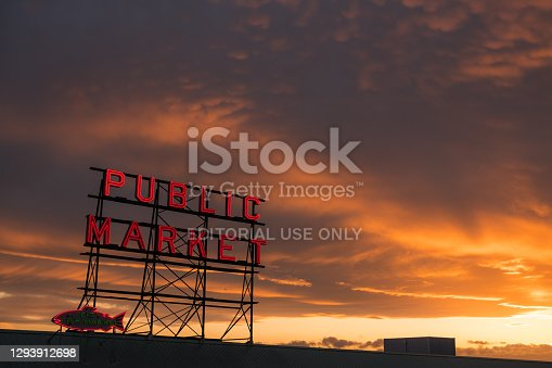 Seattle, USA - April 3, 2019: The famous neon public market sign at Pike Place Market with a brilliant sunset.