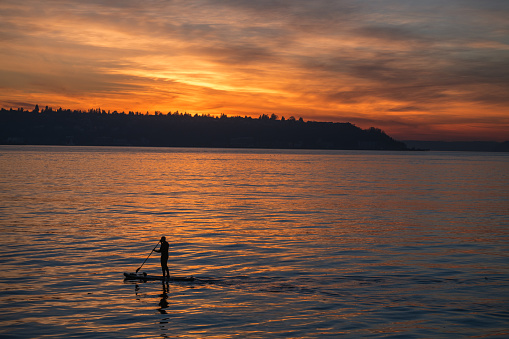 Seattle, USA - Jan 19th, 2021: A man paddle-boarding on Elliott Bay with a vivid sunset over West Seattle.