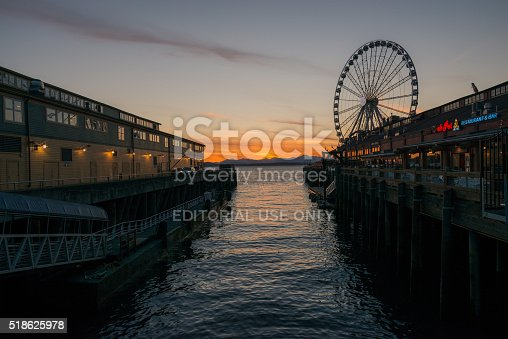 Seattle, USA - March 17, 2016: The Great Seattle Wheel on Pier 52 at sunset over the Olympic Mountains.