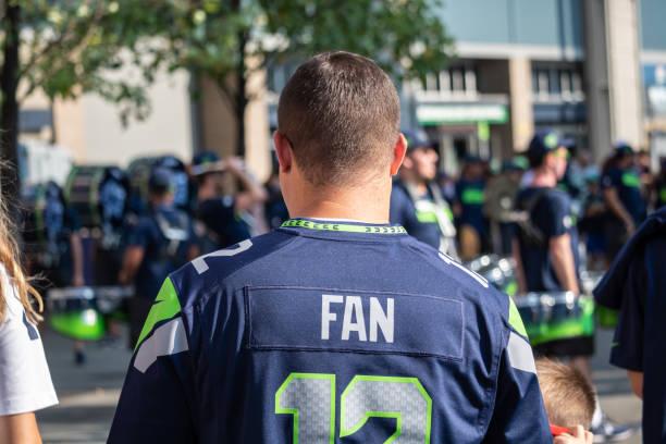Seattle, Washington - 8/9/2018 : A fan in a 12th man fan watch the Blue Thunder drumline in front of CenturyLink Field before a Seattle Seahawks football game.