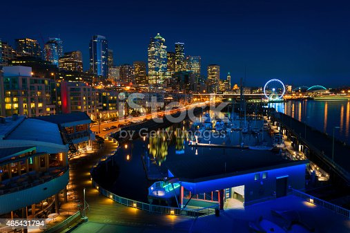 The Seattle, Washington waterfront and skyline at sunset with a marina and ferris wheel. The Port of Seattle can be seen in the background.