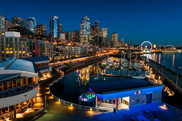 Seattle Waterfront at Sunset The Seattle, Washington waterfront and skyline at sunset with a marina and ferris wheel. The Port of Seattle can be seen in the background. promenade stock pictures, royalty-free photos & images