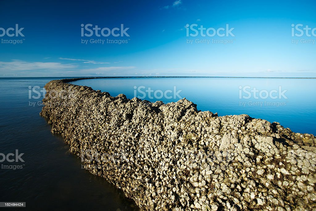 Seawall under deep blue sky royalty-free stock photo