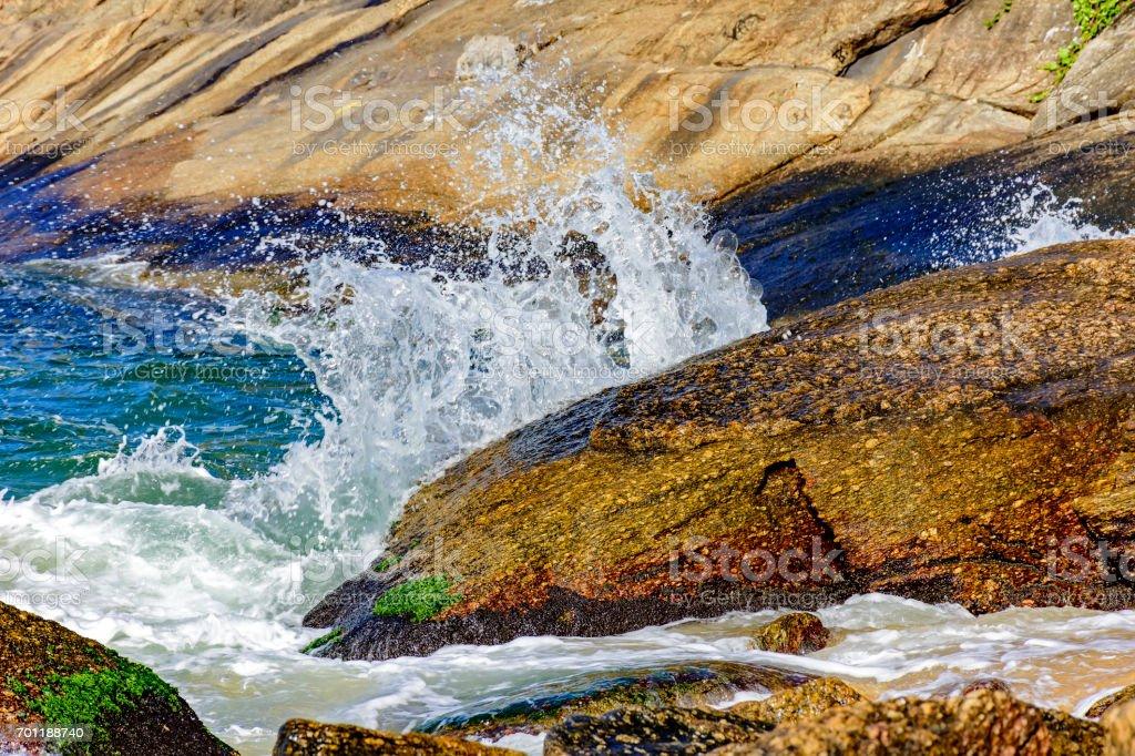 Seawater crashing on stones stock photo