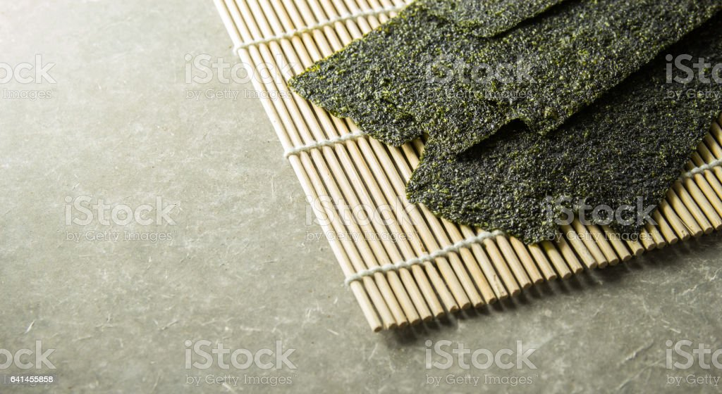 Seaweed roasted  snack (nori) on mat. stock photo