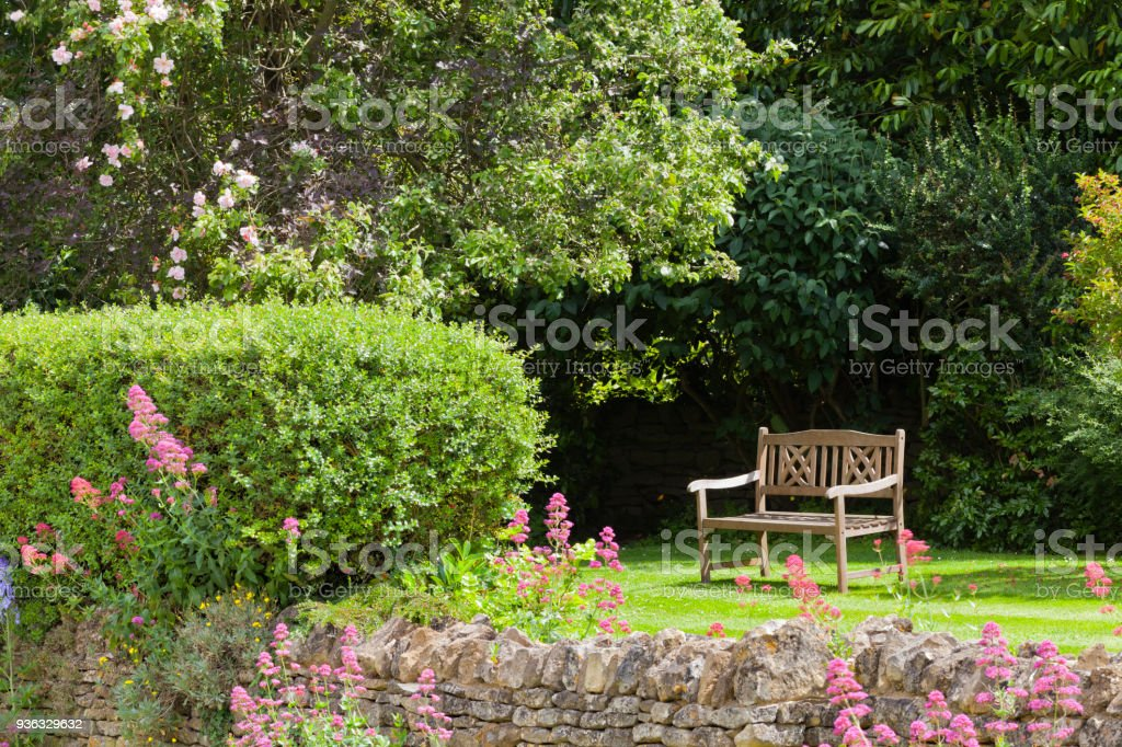 Secluded Wooden Bench In A Summer English Garden With Cottage