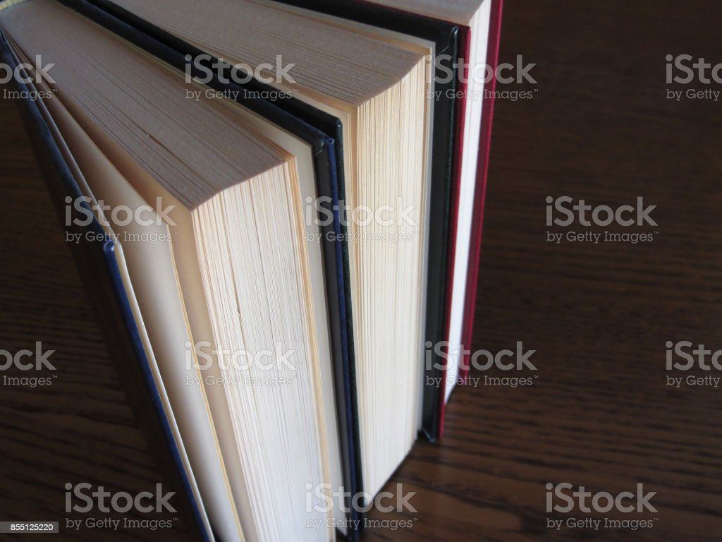 Second hand books standing on a wooden table . View from above . Top view stock photo