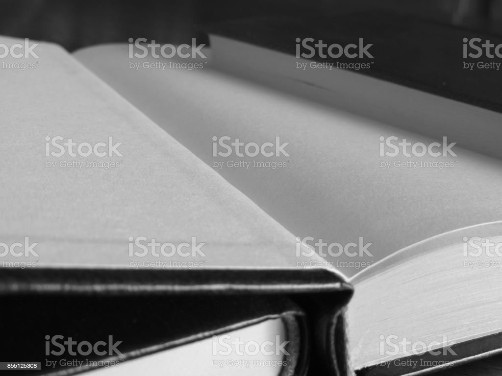 Second hand books with blank pages on a wooden table . Black and white photo stock photo