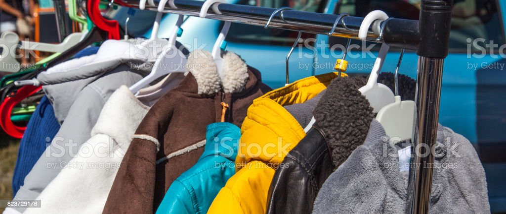 second hand children clothing on rack at outdoor flea market stock photo