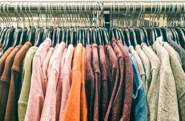 second hand laden pullover kleider hängen shop sparsamkeit auf flohmarkt - hipster kleiderschrank verkauf konzept und alternative retro-moda mode styling - weicher kontrast entsättigt nostalgie gefilterten-look - uhrenhalter stock-fotos und bilder