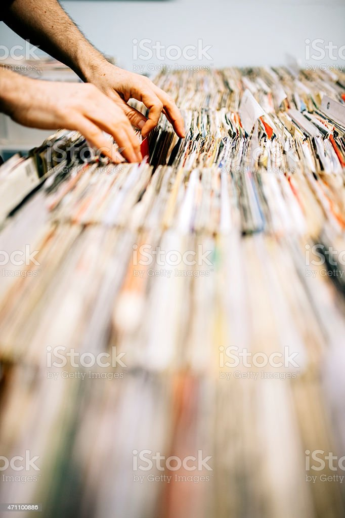 An unrecognisable customer searches through and selects a second hand...