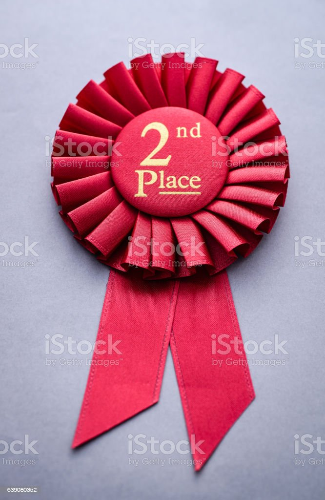 Second place red winners rosette on grey stock photo