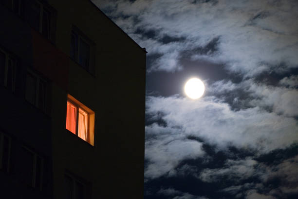 Second Story House Window Lit Against Night Sky stock photo